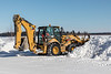 Caterpillar 450E loader trimming snowbanks along Revillon Road in Moosonee 2018 March 14.