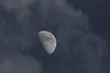Moon among late afternoon clouds.