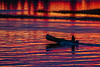 Canoe in silhouette on water reflecting purple and yellow from the sky before sunrise.