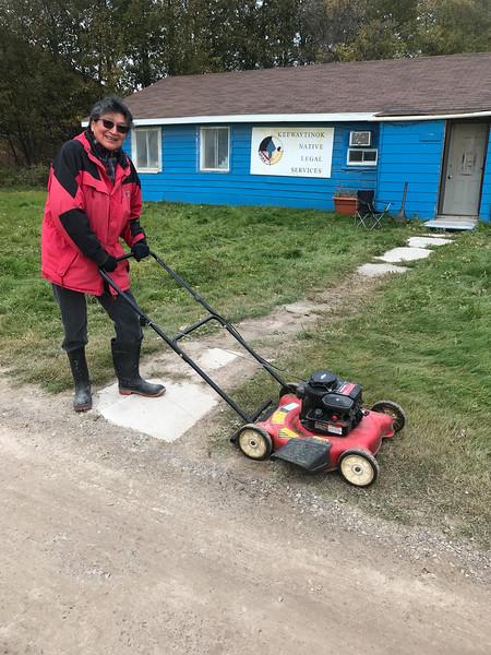 Celine Koostachin cutting grass at Keewaytinok Native Legal Services 2018 October 3.