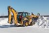 Caterpillar 450E loader trimming snowbanks along Revillon Road in Moosonee 2018 March 14.