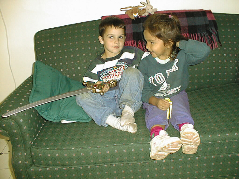 David and Danis on couch in clinic apartment. David holding sword. 1998 September 6.