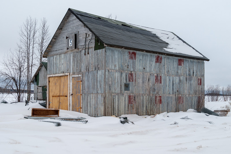 Shed number 5 along Airport Road in Moosonee, near ferry docks. 2005 March 19th. Yellow doors and red patches. Wooden.