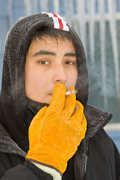 Anthony Isaac shovelling snow off Keewaytinok Native Legal Services roof New Year's Eve 2007, taking a quick smoke break