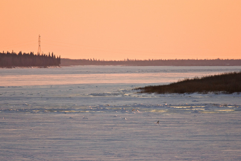 View up the Moose River from Moosonee, Ontario on December 9, 2007. Tower to left is one of two that carries electricity from the mainland (Moosonee side) to Moose Factory Island.
