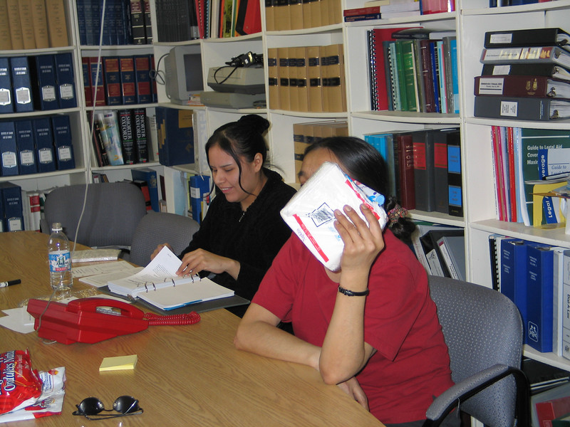 Loretta Loon doing updating, Mary Blueboy covering her face in library at Keewaytinok Native Legal Services. 2004 February 20.