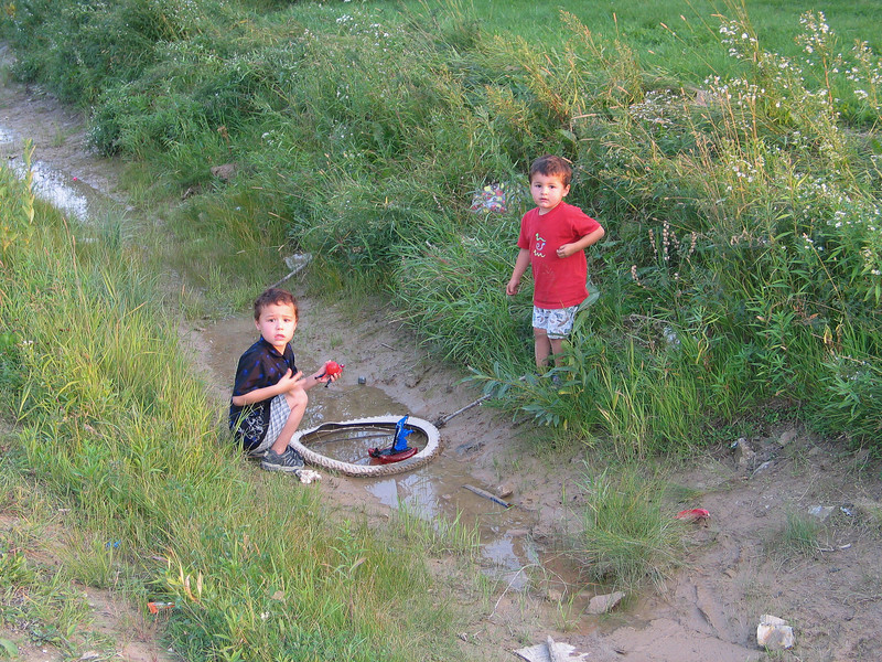 Children playing in drainage ditch in Moosonee. 2003 September 10