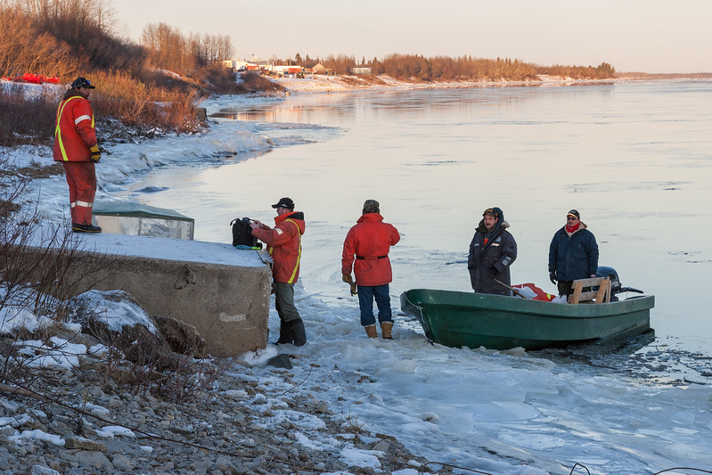 People boarding a canoe at public docks site in Moosonee 2007 November 21st. Ice along shore.