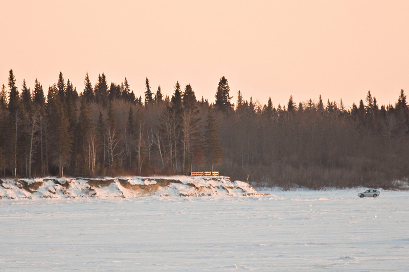 Vehicle driving on Moose River approaches the south end of Charles Island on its way to Moose Factory from Moosonee, Ontario. Fence visible on island was installed to discourage people from using area of rapid erosion caused by spring ice.