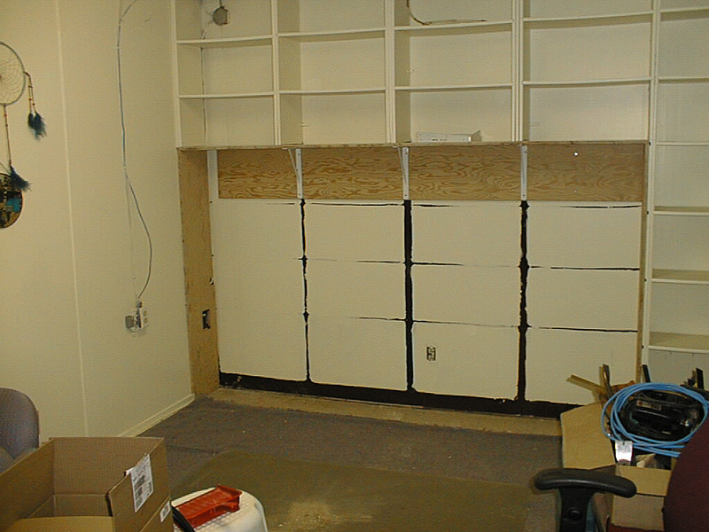 Removing some bookshelves in the library at Keewaytinok Native Legal Services to make room for computer workstations. 2003 February 24