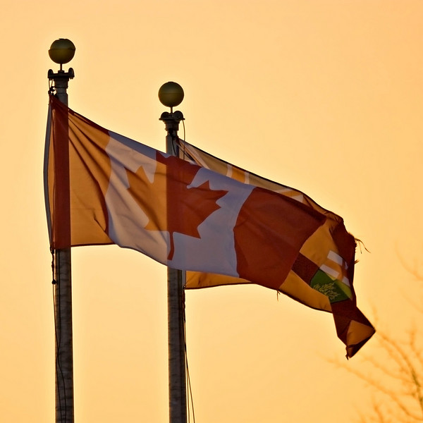 Canadian and Ontario flags at sunset outside Ontario Government Building in Moosonee, Ontario