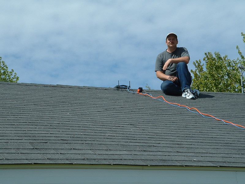 Craig Jennings on roof of Keewaytinok Native Legal Services with wireless router. For experiment, was able to walk down street to Polar Bear Lodge with laptop and continue to play video. 2003 June 8