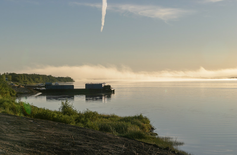 Looking down the Moose River past barge docks with fog rolling in. Bare earth in foreground from shoreline stabilization. Contrail overhead. 2004 August 30