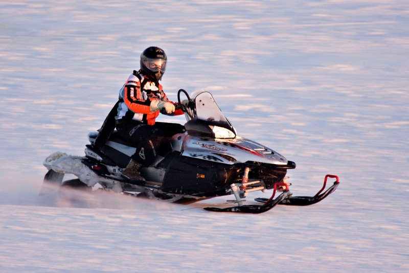 Snowmobile on the Moose River at Moosonee, Ontario heading up river.