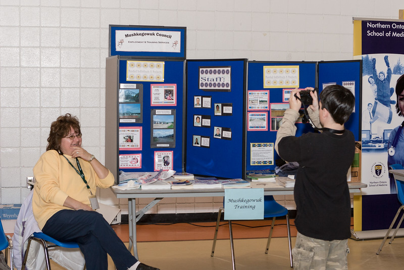Mushkegowuk Council display. Kathy Small. David Hunter taking pictures.