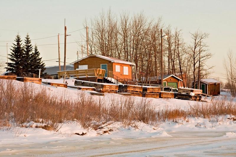 Two Bay Enterprises tours buildings in winter in Moosonee. Stored docks are shown in front of buildings.