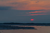 Sunrise looking down the Moose River at Moosonee 2005 April 19 Reddish sun partially obscured by clouds
