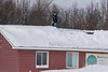 Mike Blueboy Jr. shoveling snow off the roof at Keewaytinok Native Legal Services 2006 February 9