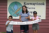 """Alexander, Heather and Tori Nootchtai holding """"Happy Birthday Dearest Mommy"""" banner by Keewaytinok Native Legal Services sign 2004 July 29"""