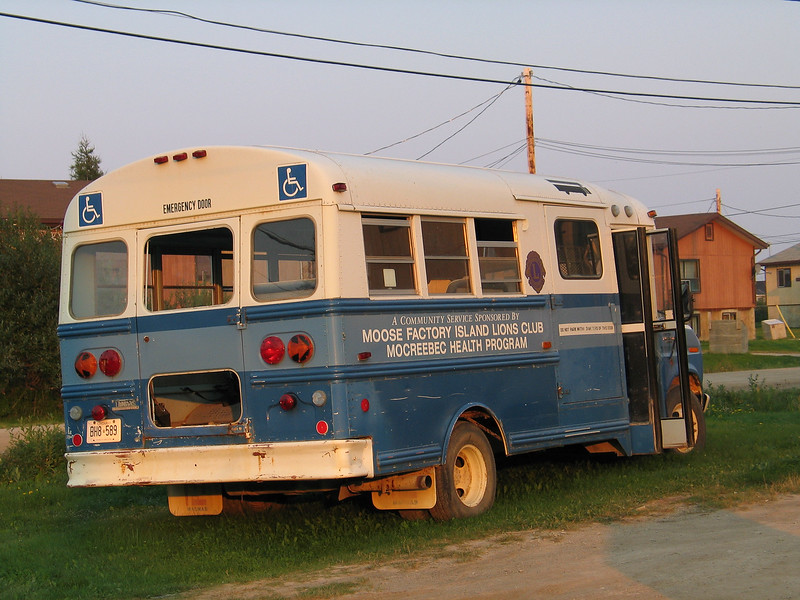 Small bus parked in Moosonee labelled for Moose Factory Island Lions Club Mocreebec Health Program. Rear window missing.