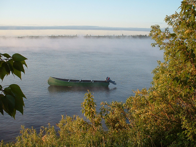 2003 June 19 fog on the Moose River, looking through gap in vegetation along the river. Canoe tied up.