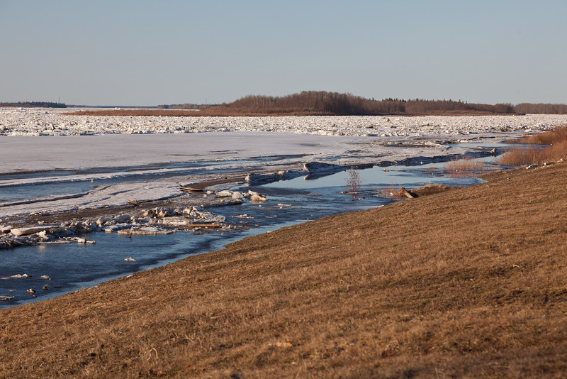 Looking up the Moose River, sheet ice in front with broken ice in distance.