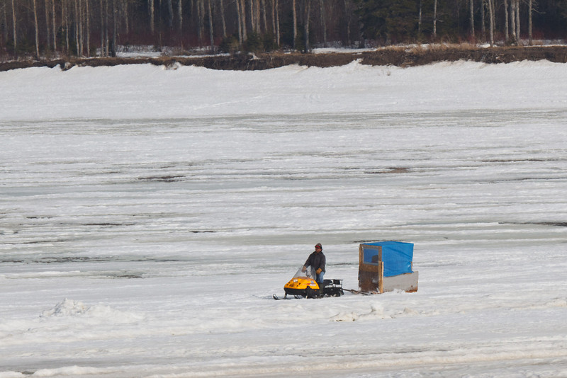 Snowmobile taxi coming across the Moose River.