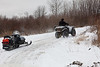 Dennis Hookimaw Sr. retrieving snowmobile that went through the ice with his ATV.