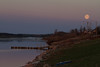 Full moon in the morning over the Moose River shoreline at Moosonee
