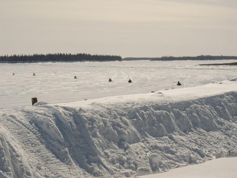 Snowmobiles crossing the Moose River towards Moosonee.
