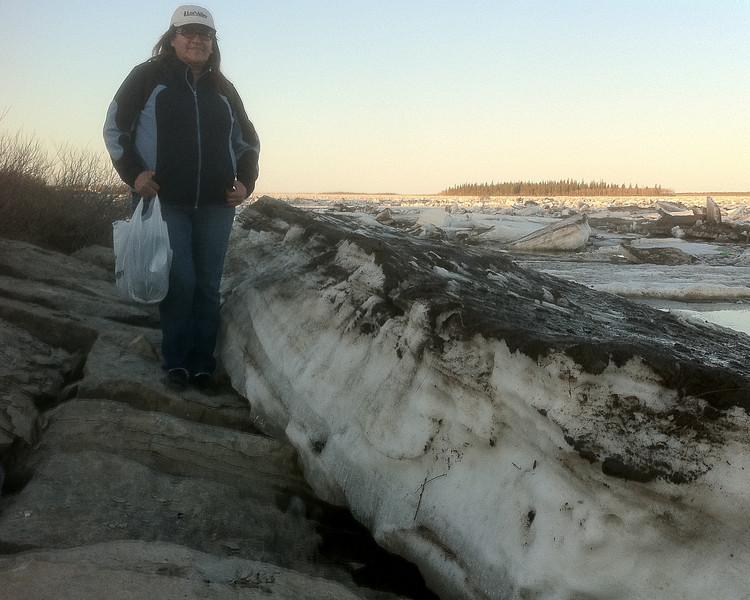 Denise Metatawabin standing beside ice floe on rocks
