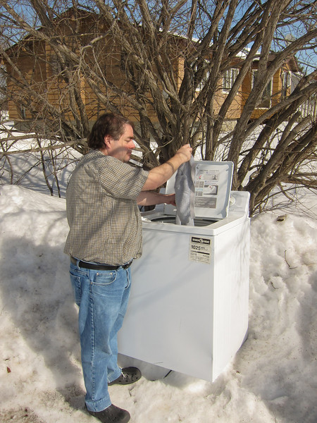 Paul Lantz using outdoor washing machine at Keewaytinok Native Legal Services 2011 April 1. Photograph by Kathryn Petra Culek.