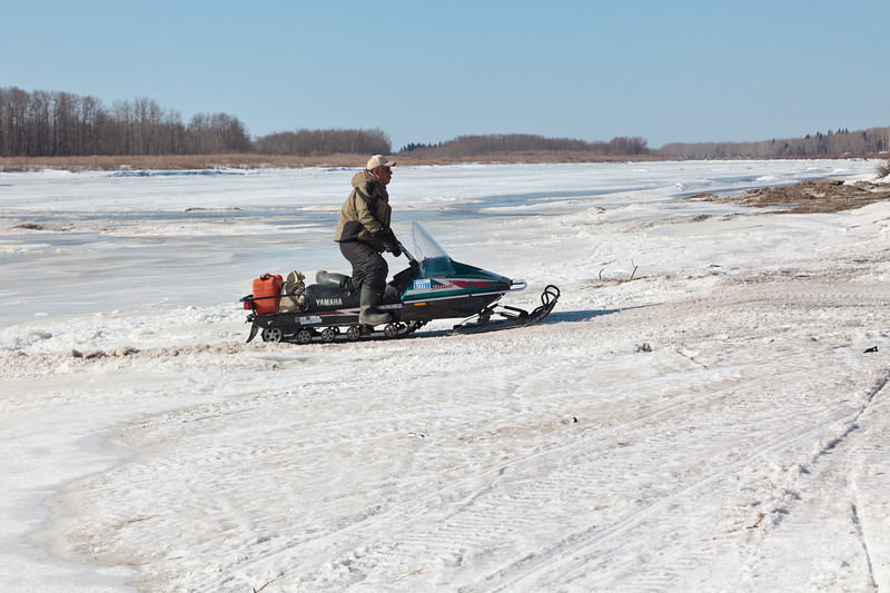 Robert Blueboy driving snowmobile on the Moose River