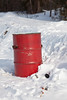 Garbage can at start of winter road.