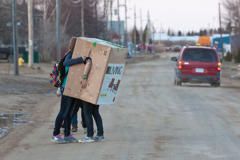 Young women carrying furniture box on Revillon Road