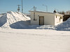 Chipstand on First Street in Moosonee behind big pile of snow 2011 March 7th.