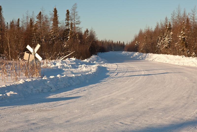 Winter road heading north from Moosonee after crossing railway tracks.