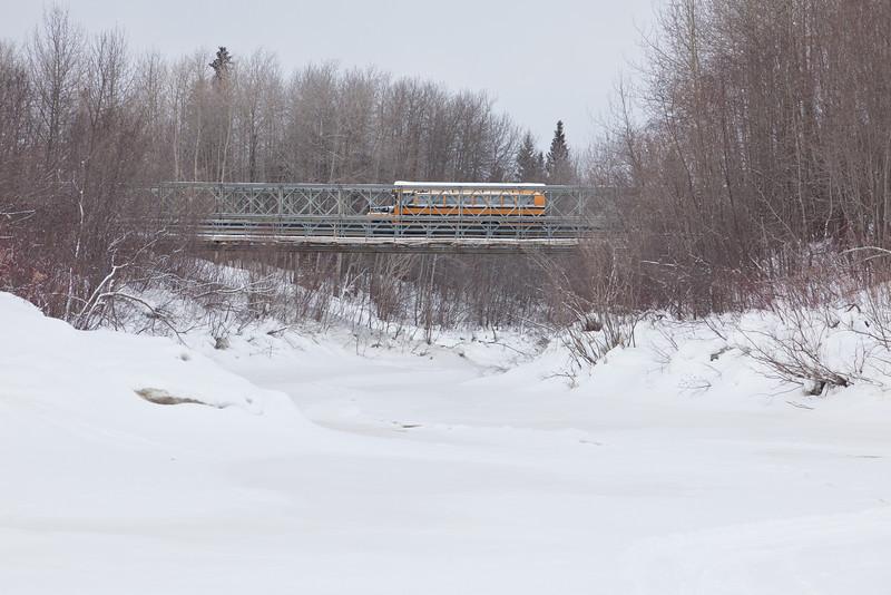 School bus crossing bridge across Butler Creek in Moosonee.