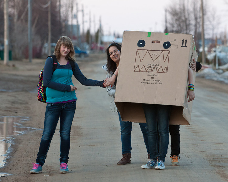 Young women carrying furniture box on Revillon Road 2011 April 30