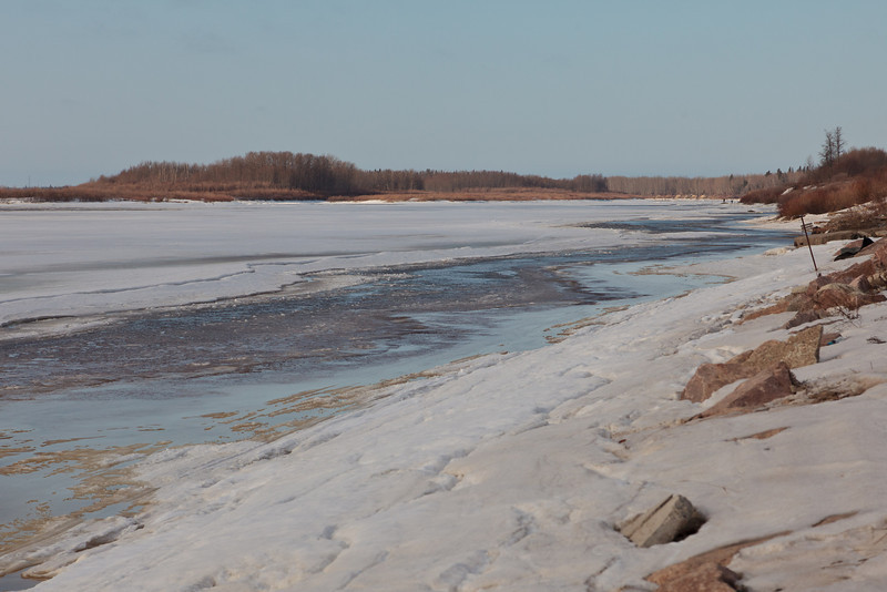 Along the Moose River shoreline looking upriver 2011 April 24th. A couple of people on the ice near McCauley's Hill.