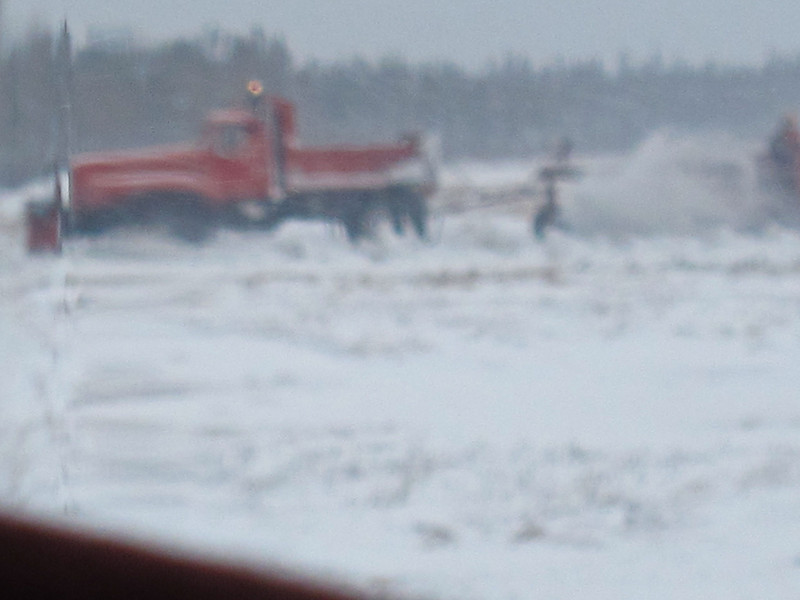 View out aircraft window of snowplowing activity on other runway (plane on taxiway)