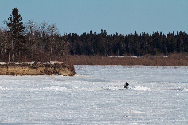 Brian O'Neill, an articling student at Keewaytinok Native Legal Services in Moosonee, Ontario bicycles back to Moosonee from the clinic's satellite office in Moose Factory across the Moose River (North Road) 2011 March 29th. Brian seen here near south end of Butler Island.