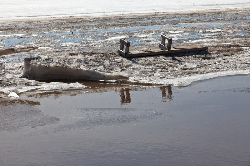 Moose River ice and water from public docks. Bench on the ice.
