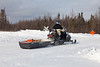 Snowmobile and sled heading up winter road.