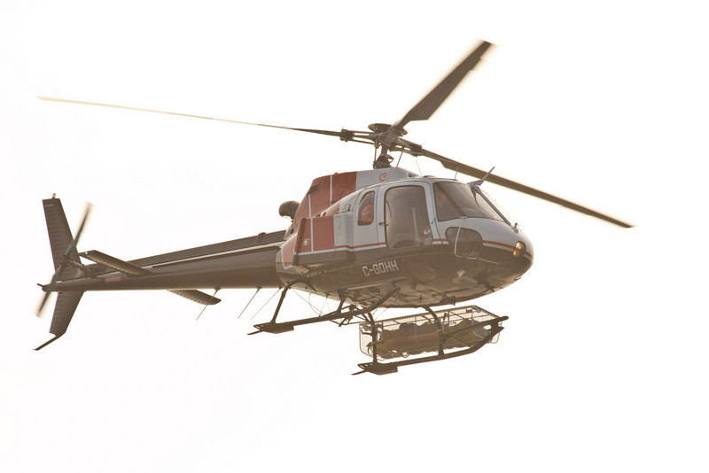 Helicopter carrying load, along the Moosonee shoreline and then across the river towards south of Moose Factory.