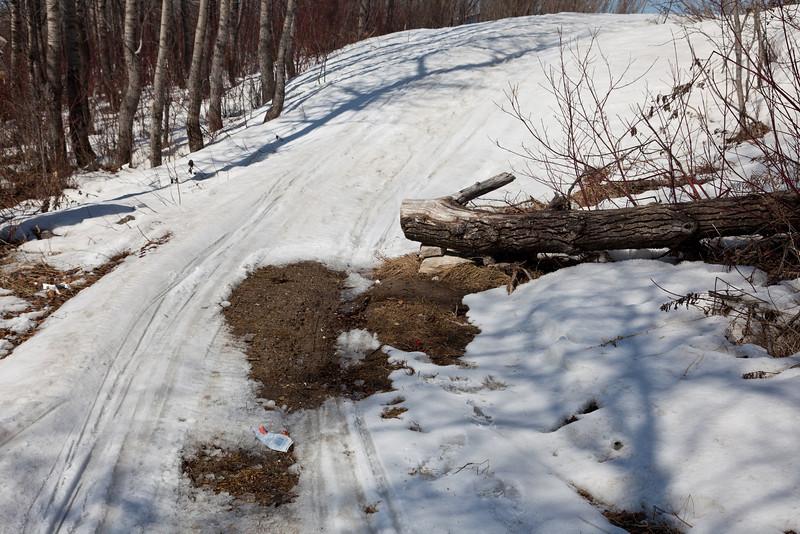 Snowmobile trail beside Store Crek getting bare