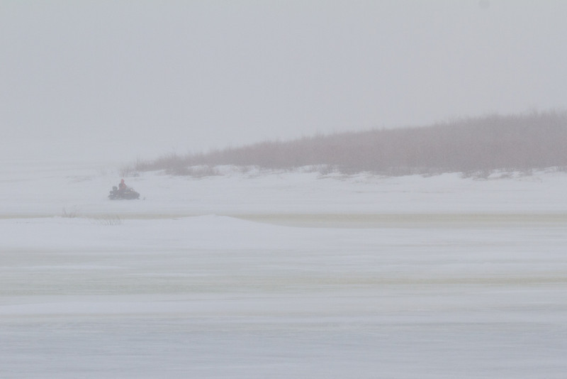 Snowmobile on the Moose River in snow storm.