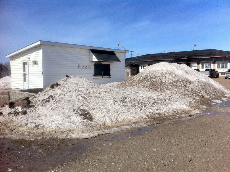 Snow pile by pizza stand near Moosonee Office Building