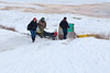 The snowmobile taxi that brought her being stuck at the bottom of McCauley's Hill in Moosonee, Keewaytinok Native Legal Services student at law Sofia Ashraf heads up the hill.