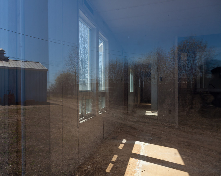 Reflections in window of trailer behind fire hall